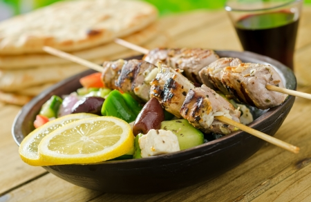 Photo of grilled pork souvlaki skewers with Greek salad and lemon.