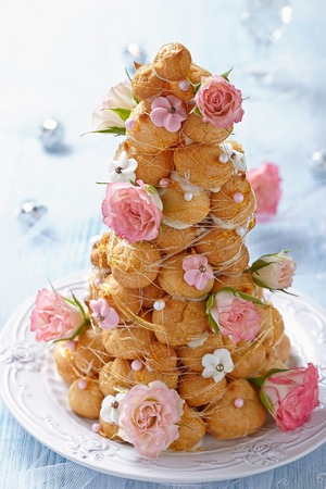 croquembouche with pink and white frosting and roses
